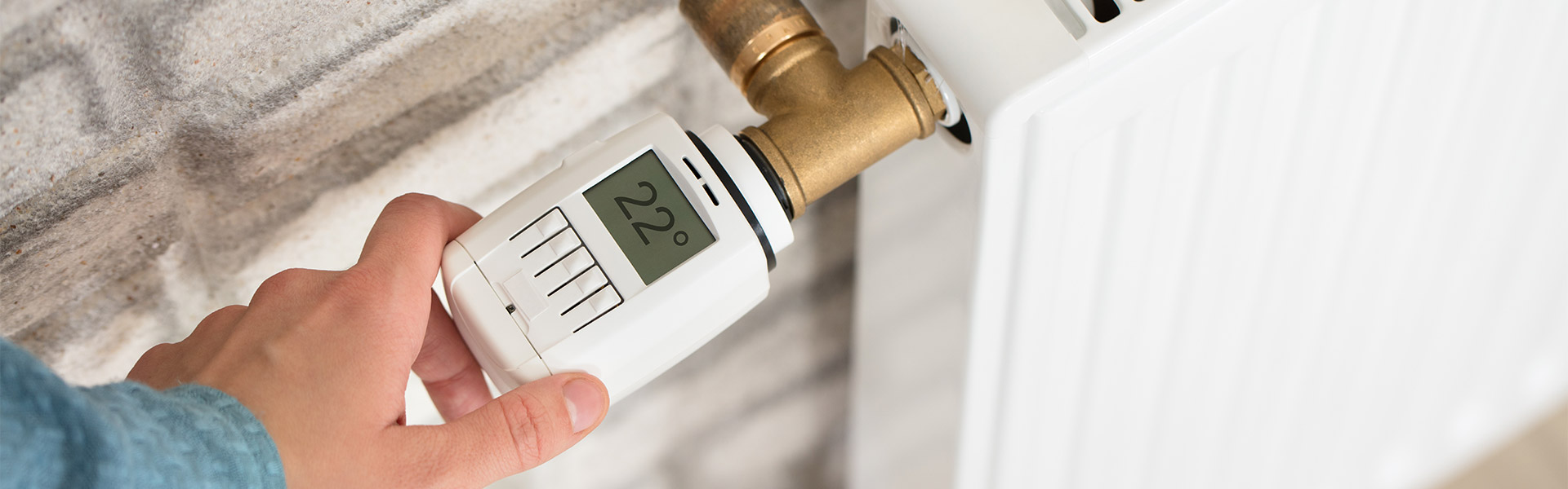 Person Adjusting Temperature On Thermostat