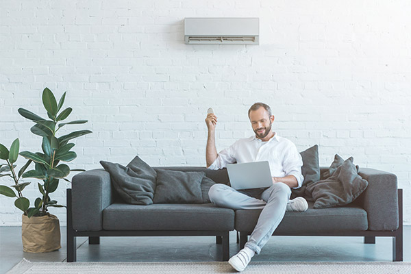 Man turning on air conditioner with remote control while using l